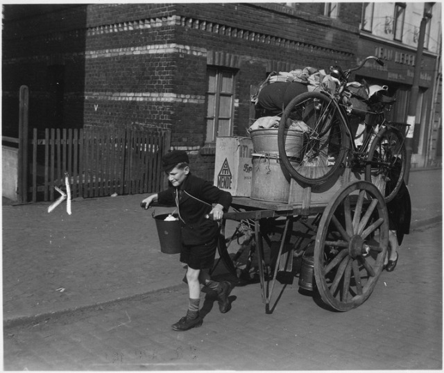 Lad_with_mother_pushing_from_behind_rolls_cartload_of_possessions_out_of_Uerdingen,_Germany,_moved_out_by_allied..._-_NARA_-_531255.tif