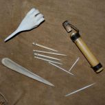 Tools, clockwise from lower left: large awl, sewing awl, rivercane needle case, bone toothpick, sewing needles in center.